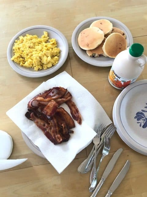plate with pancakes, plate with eggs, and bacon on paper towel on a table