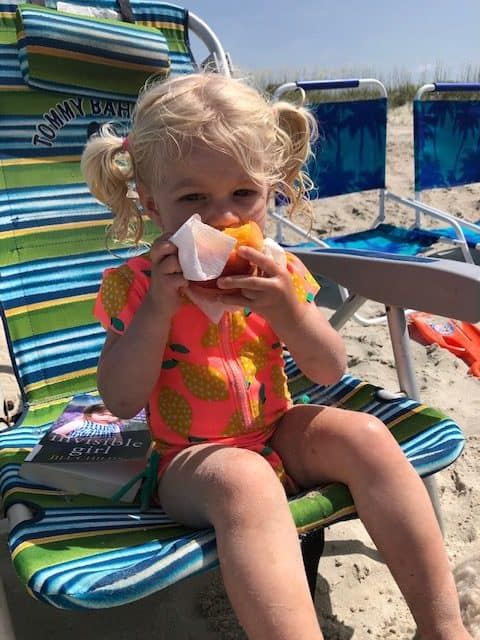 toddler eating peach on beach chair