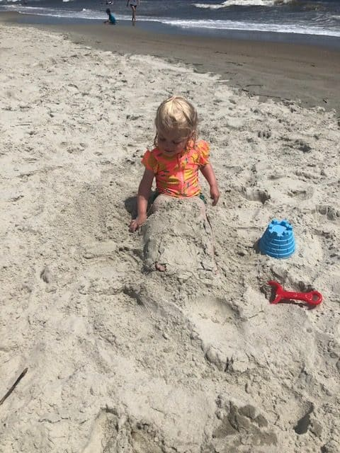 toddler playing in sand at the beach