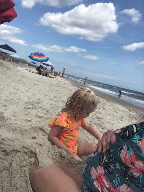 mom and toddler sitting on the beach