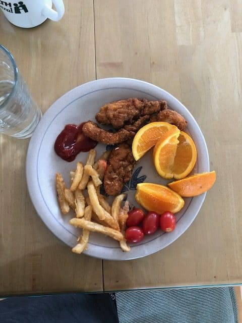 chicken tenders, fries and fruit on a plate