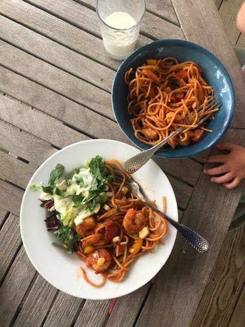 pasta with shrimp and salad on white plate with blue plate next to it