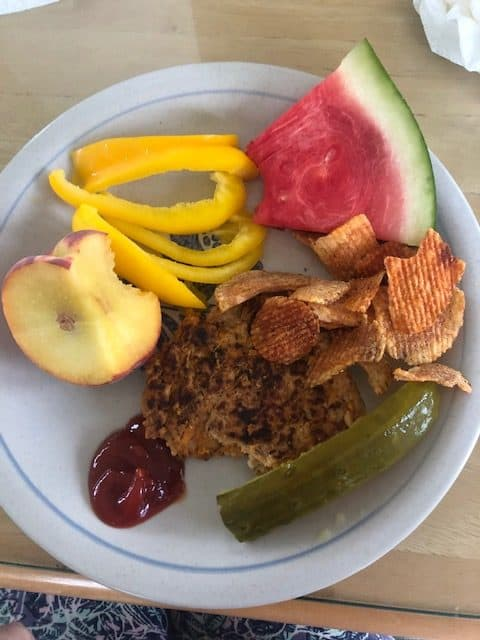 plate with watermelon, peach, pepper chips and a burger