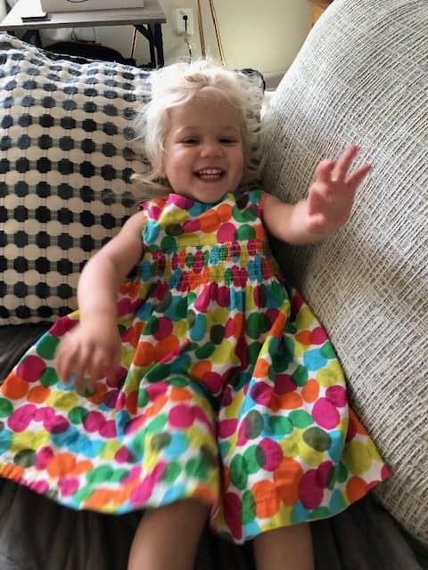 toddler laying on the couch in rainbow dress
