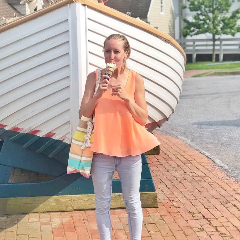 girl wearing orange tank top and eating ice cream