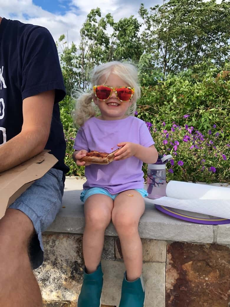 toddler eating pizza with sunglasses on