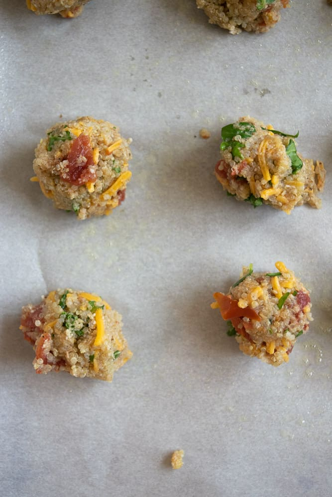 closeup of raw quinoa and meatball batter on parchment paper and baking sheet before baking