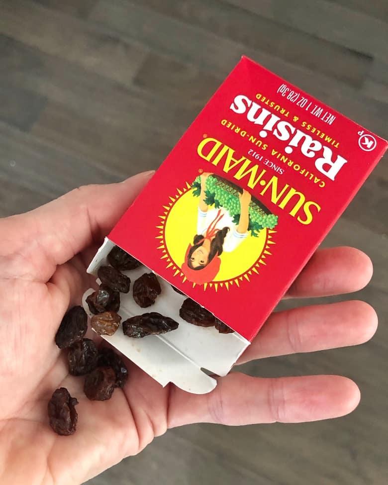 box of Sunmaid raisins in hand
