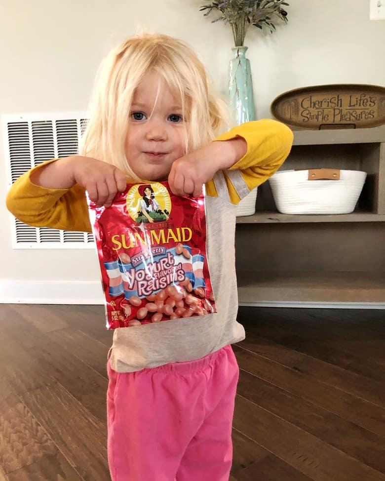 toddler holding strawberry raisins