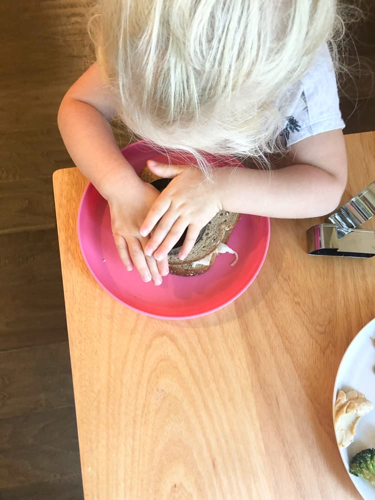 toddler pushing stencil into sandwich