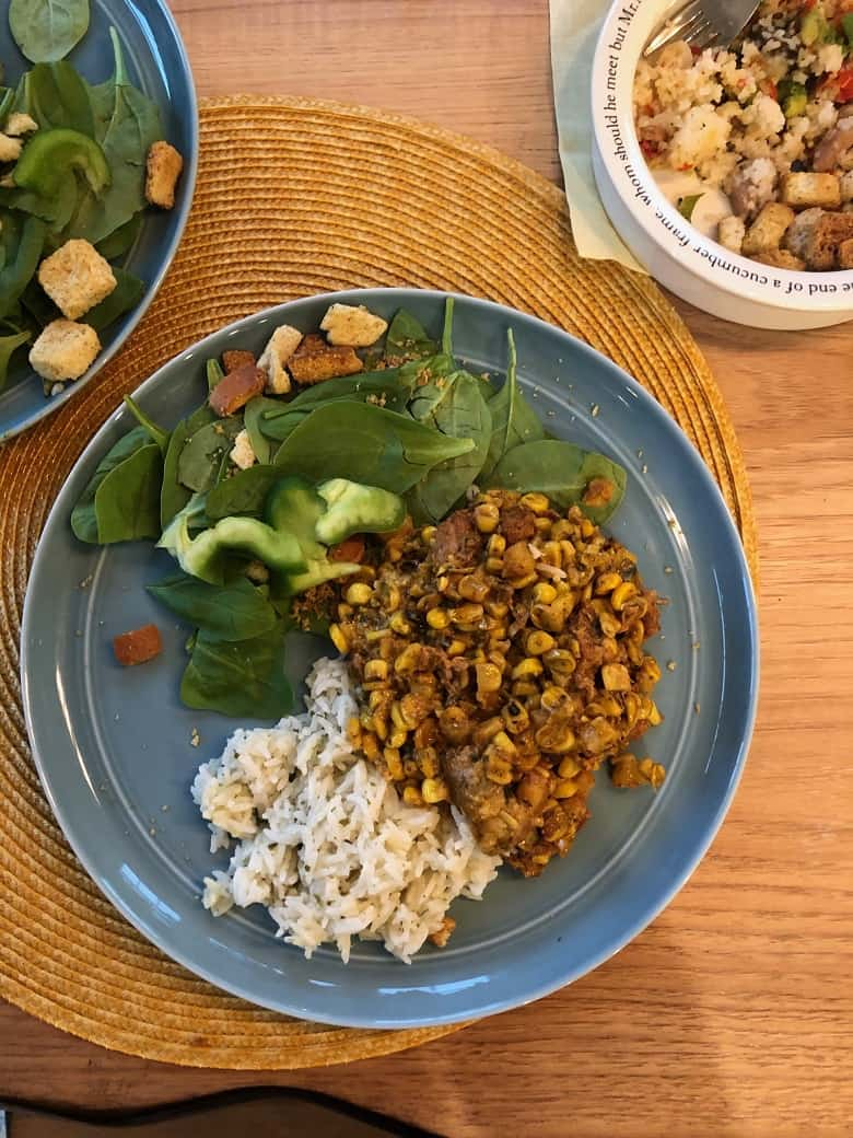 Corn and pork with white rice on blue plate