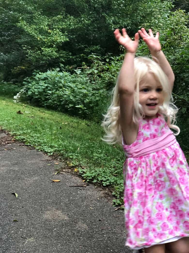 toddler in pink dress walking on greenway