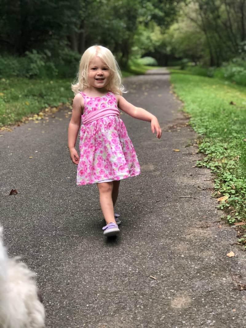 toddler wearing pink dress on walking trail