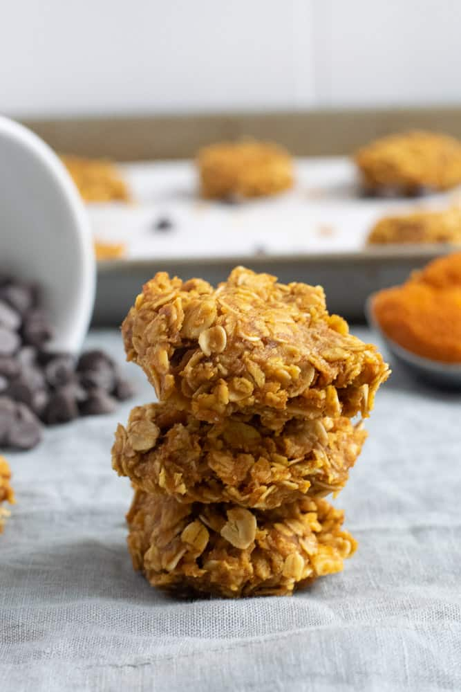 stack of 3 pumpkin no bake cookies with chocolate chips in background