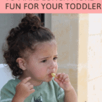 Toddler eating fruit in high chair