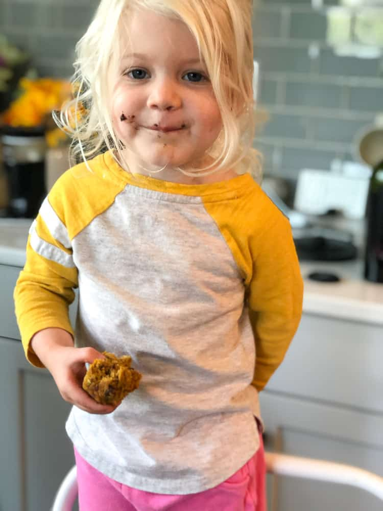 toddler holding and eating dairy free pumpkin muffin