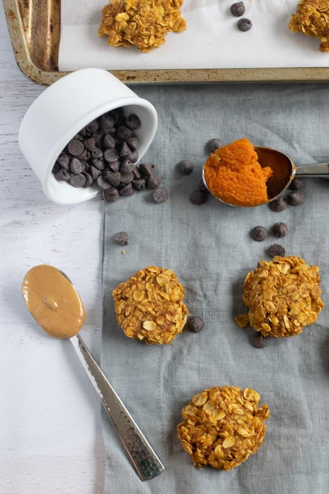 flourless pumpkin cookies on gray napkin with pumpkin puree and chocolate chips
