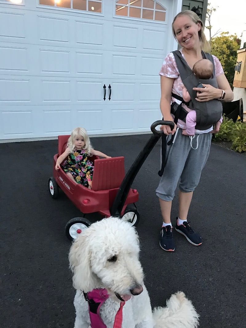 mom holding baby and pulling wagon