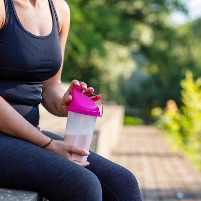 woman holding pre workout coffee shake because Coffee before running can help improve performance