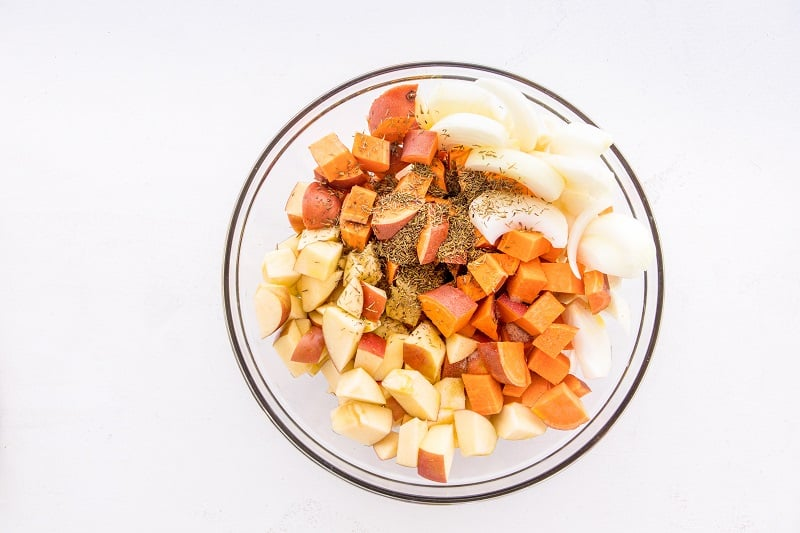 clear mixing bowl with ingredients for sheet pan pork and sweet potatoes dinner