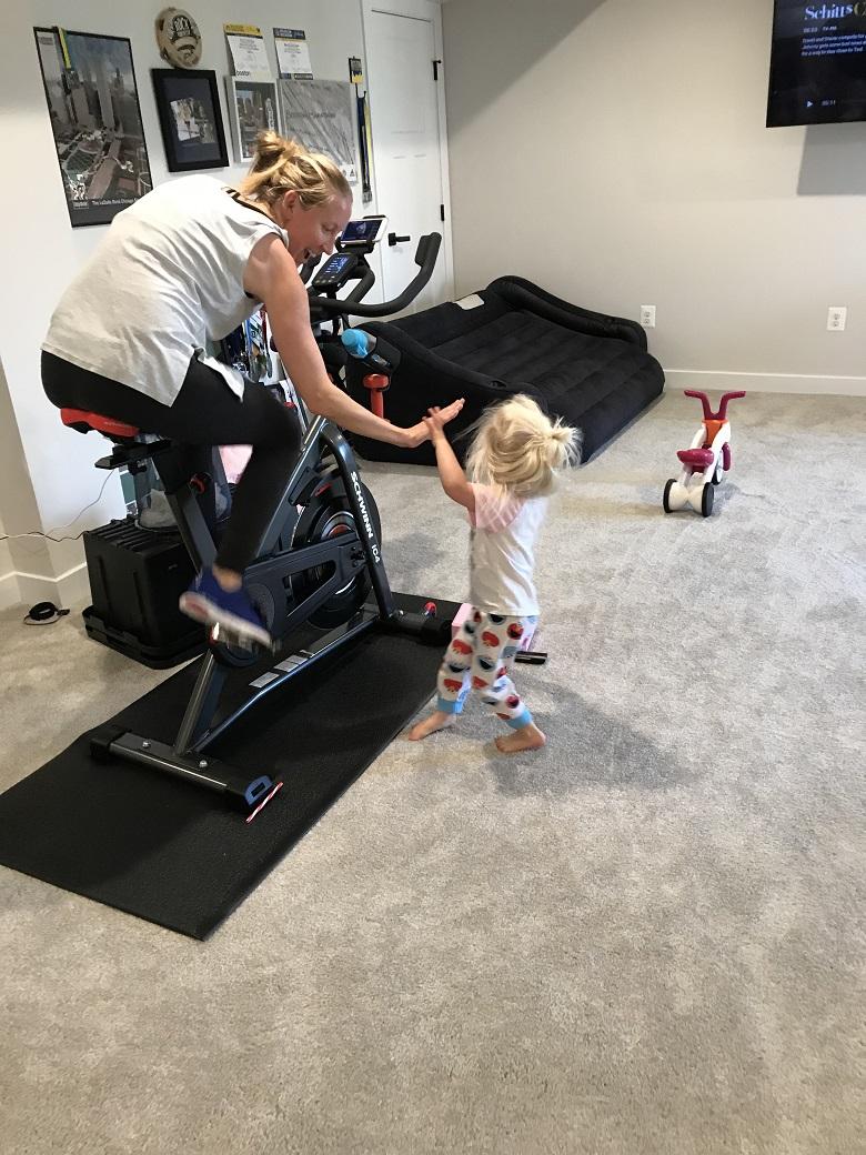 mom on spin bike high fiving toddler