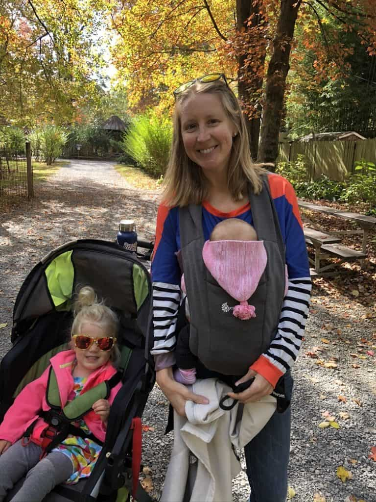 mom holding baby in infant carrier with toddler in stroller