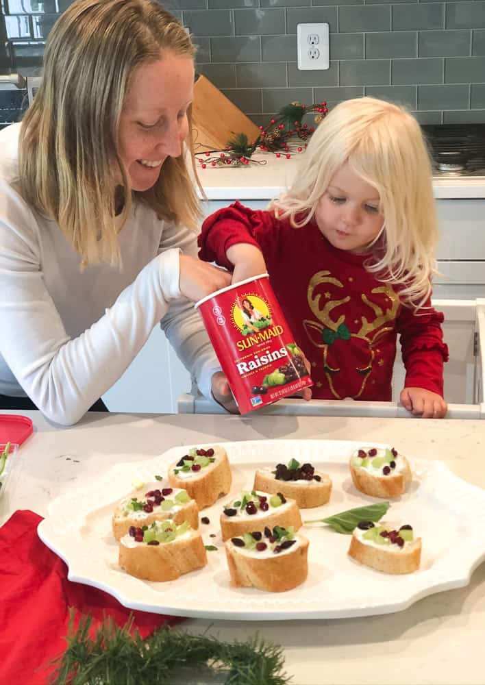 toddler decorating holiday bruschetta with Sun-Maid raisins