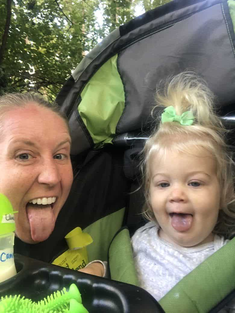 mom and baby sticking tongue out with baby in running stroller