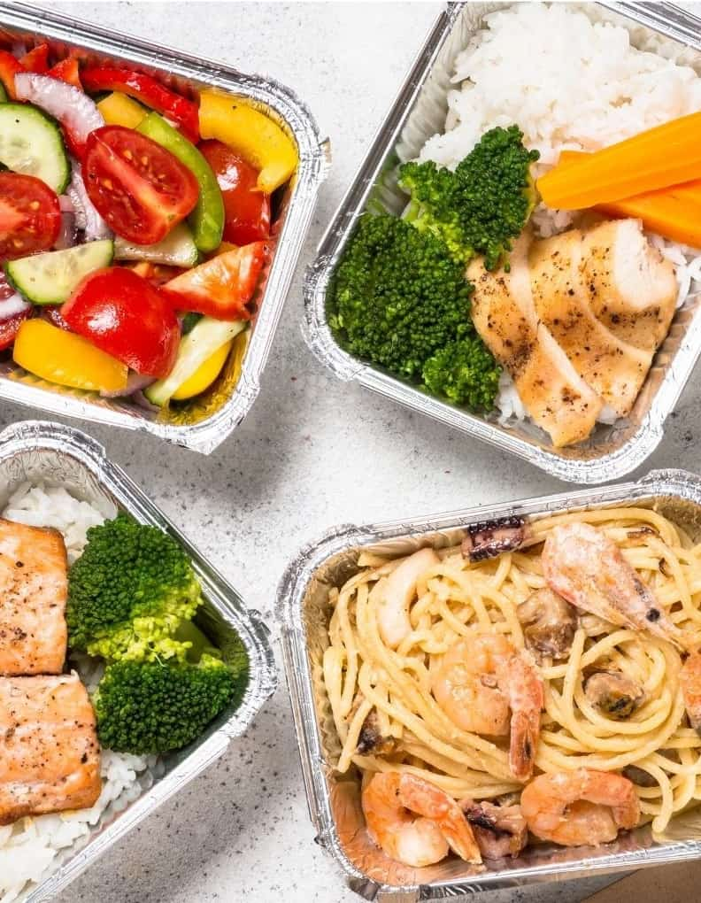 overhead view of carry out meal delivery options, like pasta with chicken and salmon