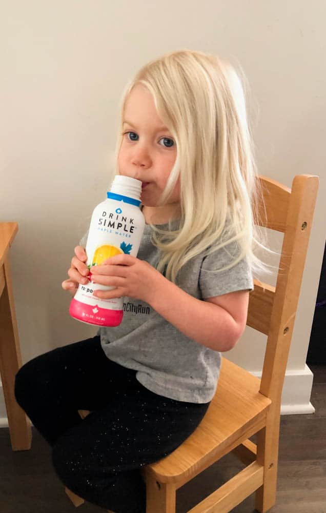toddler drinking maple water out of bottle on wooden chair