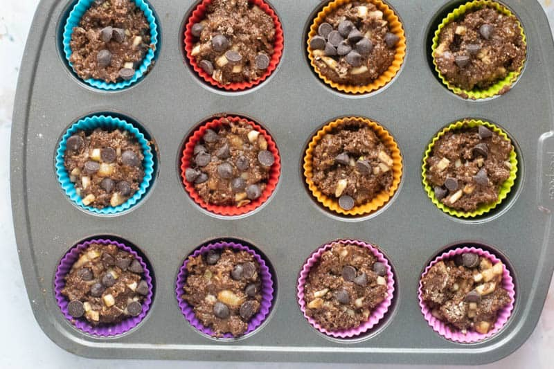 baking pan with colorful silicone baking cups filled with batter for chocolate banana chickpea muffins