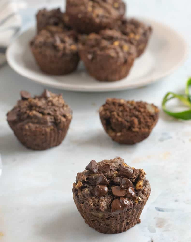 chocolate chip garbanzo flour muffin on white countertop with bowl of more muffins in background