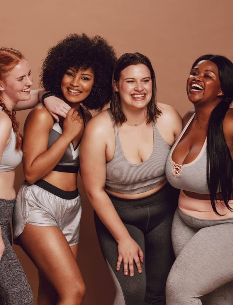 4 women huddled together of all different body sizes