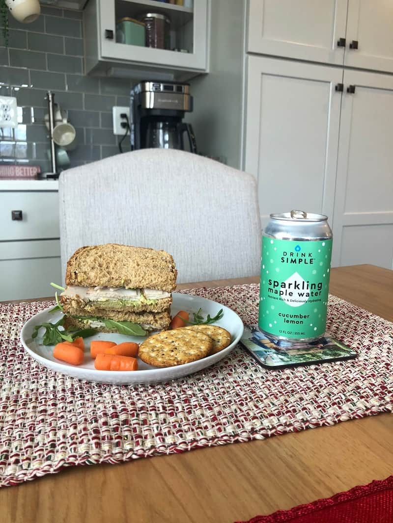 Drink Simple Cucumber Maple Water can next to plate with sandwich on it on table