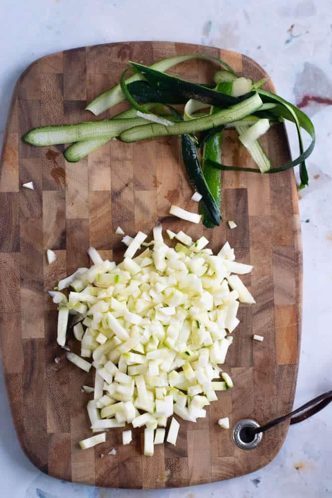 diced zucchini on a wooden cutting board