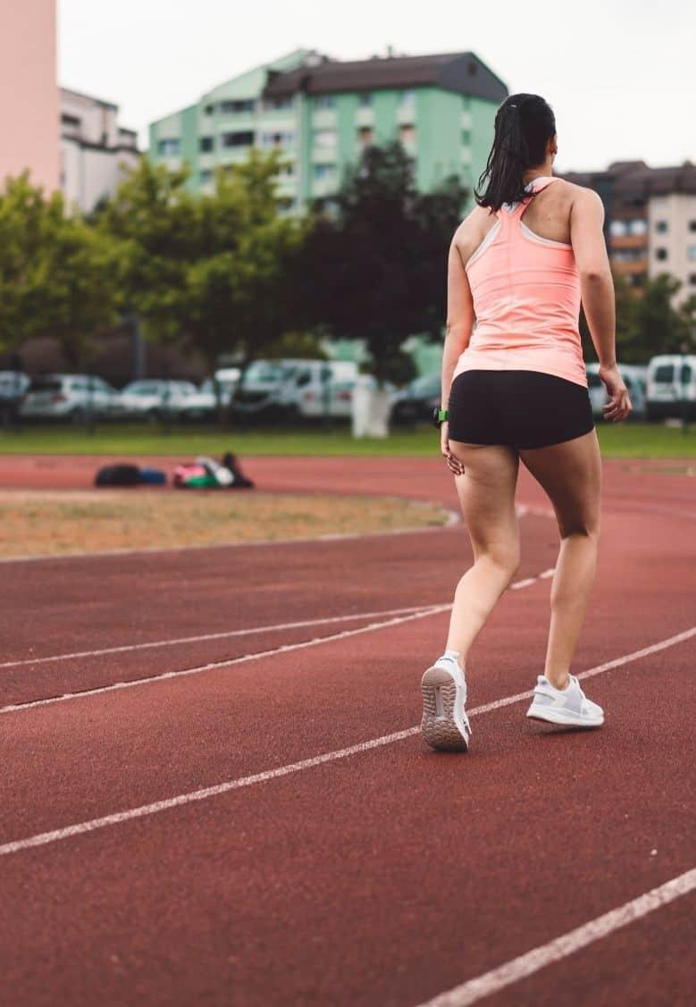 girl in pink tank top running around track grabbing her hamstring