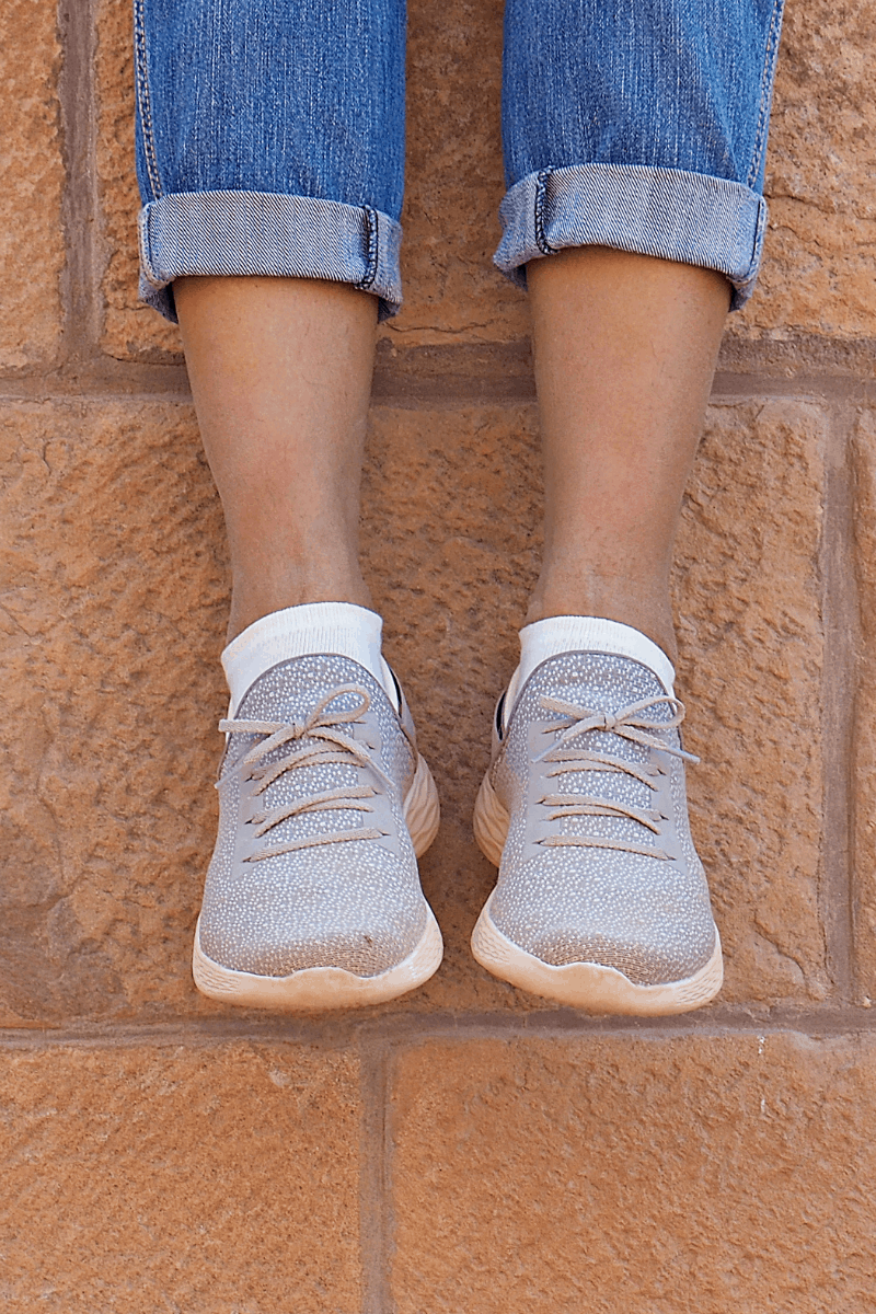 Legs and shoes hanging down off brick wall