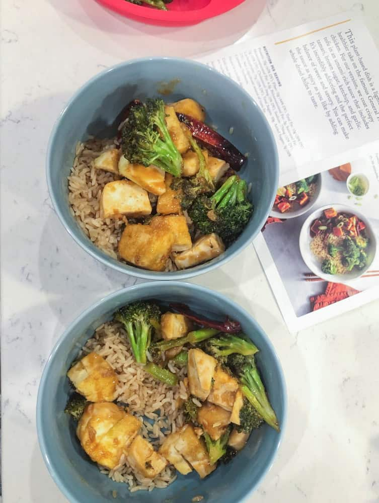 Rice and tofu with broccoli served in blue serving bowls