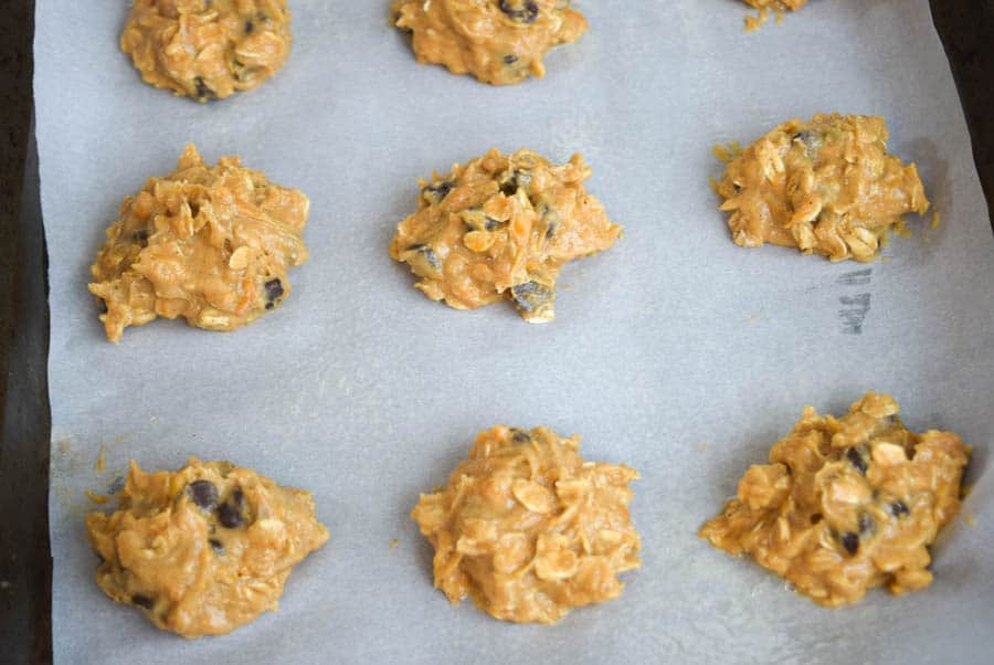 sweet potato cookie batter on baking sheet with parchment paper before baking