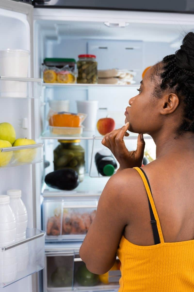 woman in yellow tank top looking into open refrigerator to decide what to eat