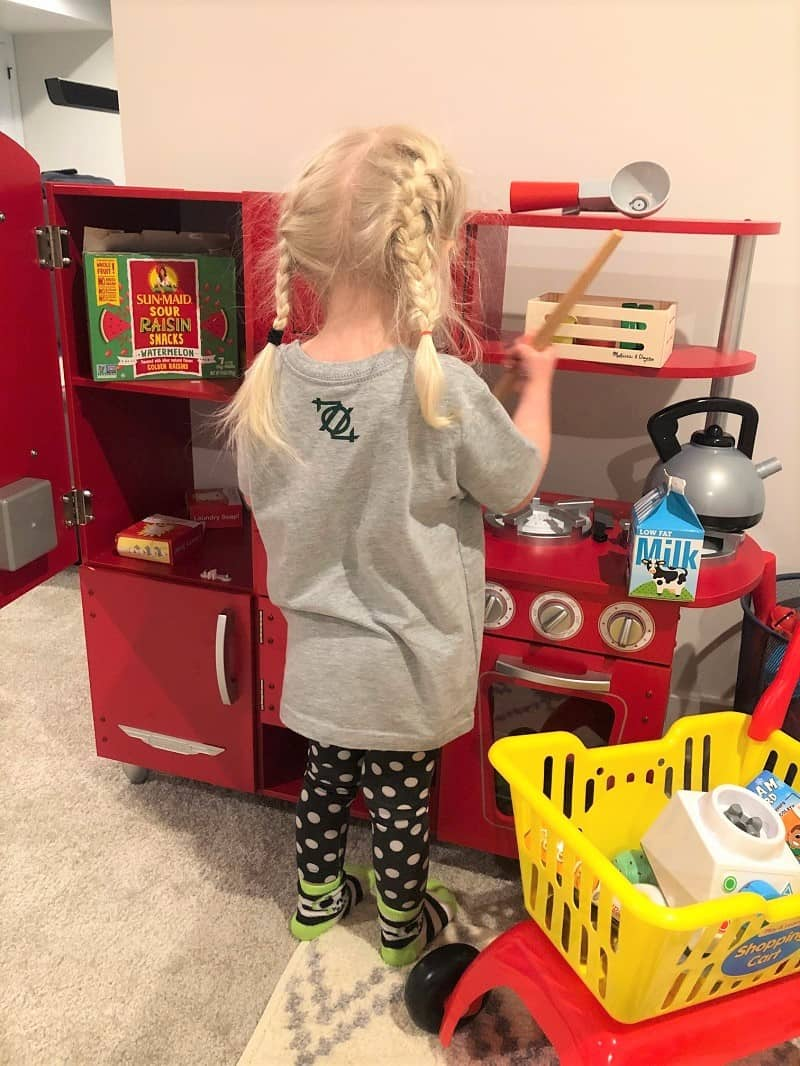 toddler playing in toy kitchen with back to camera