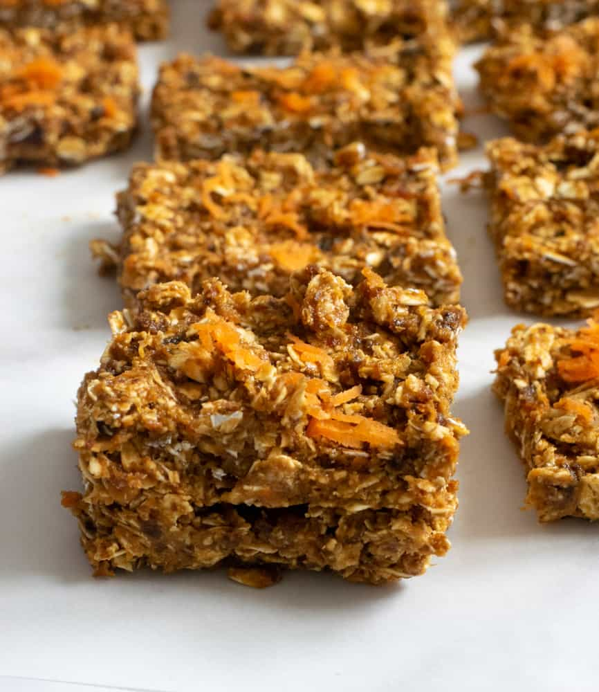 closeup of no bake vegan carrot cake bars on parchment paper topped with shredded carrot