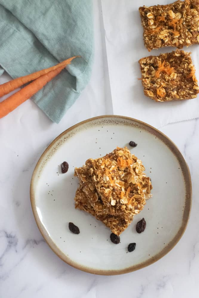 no bake carrot cake bars cut into squares on gray plate with gold lining and raisins on plate