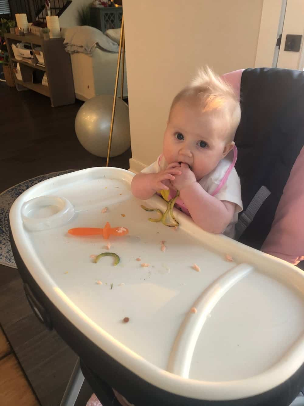 baby eating diced squash in high chair