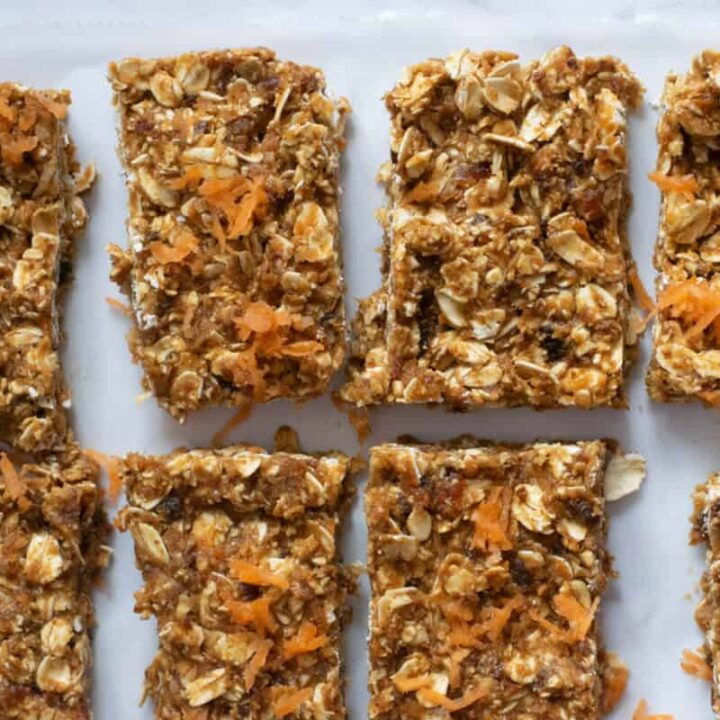 overhead shot of carrot cake no bake bars topped with shredded carrots on parchment paper