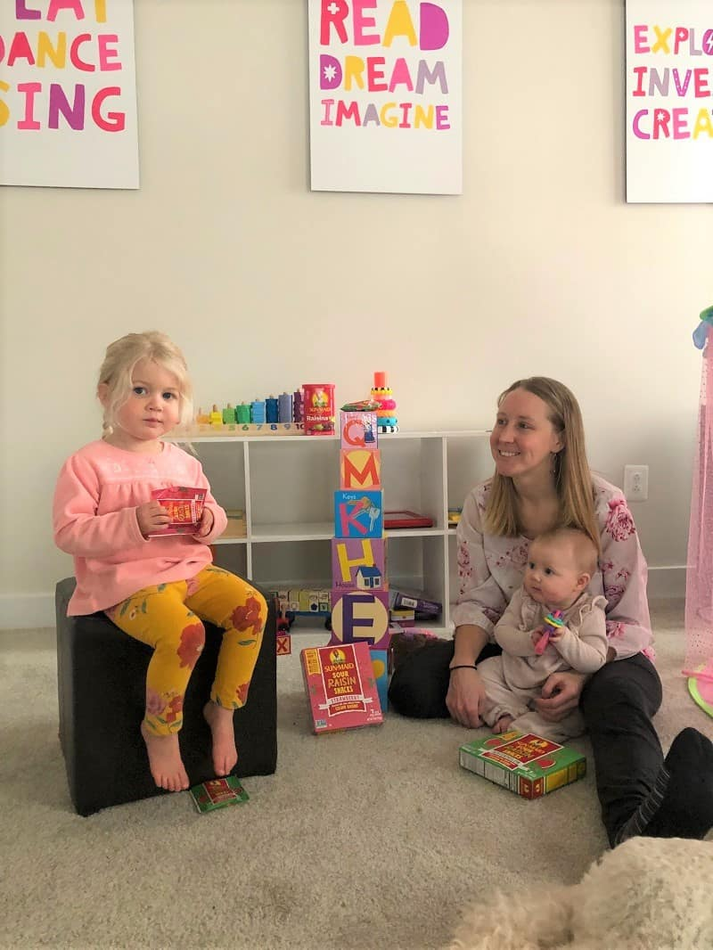 mom with two daughters in playroom playing with blocks