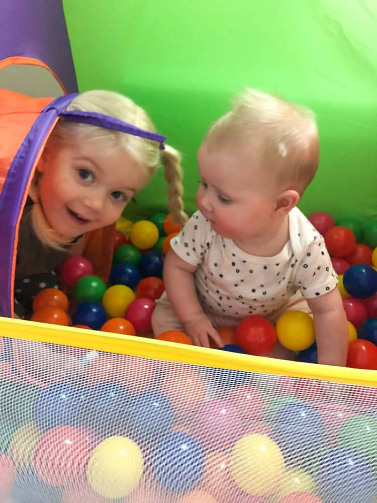 toddler and baby playing in ball pit