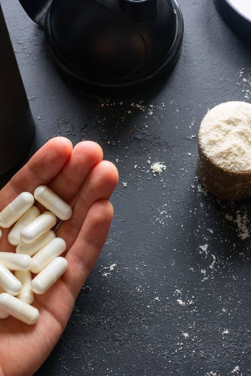 hand holding supplement tabs and scoop of protein powder