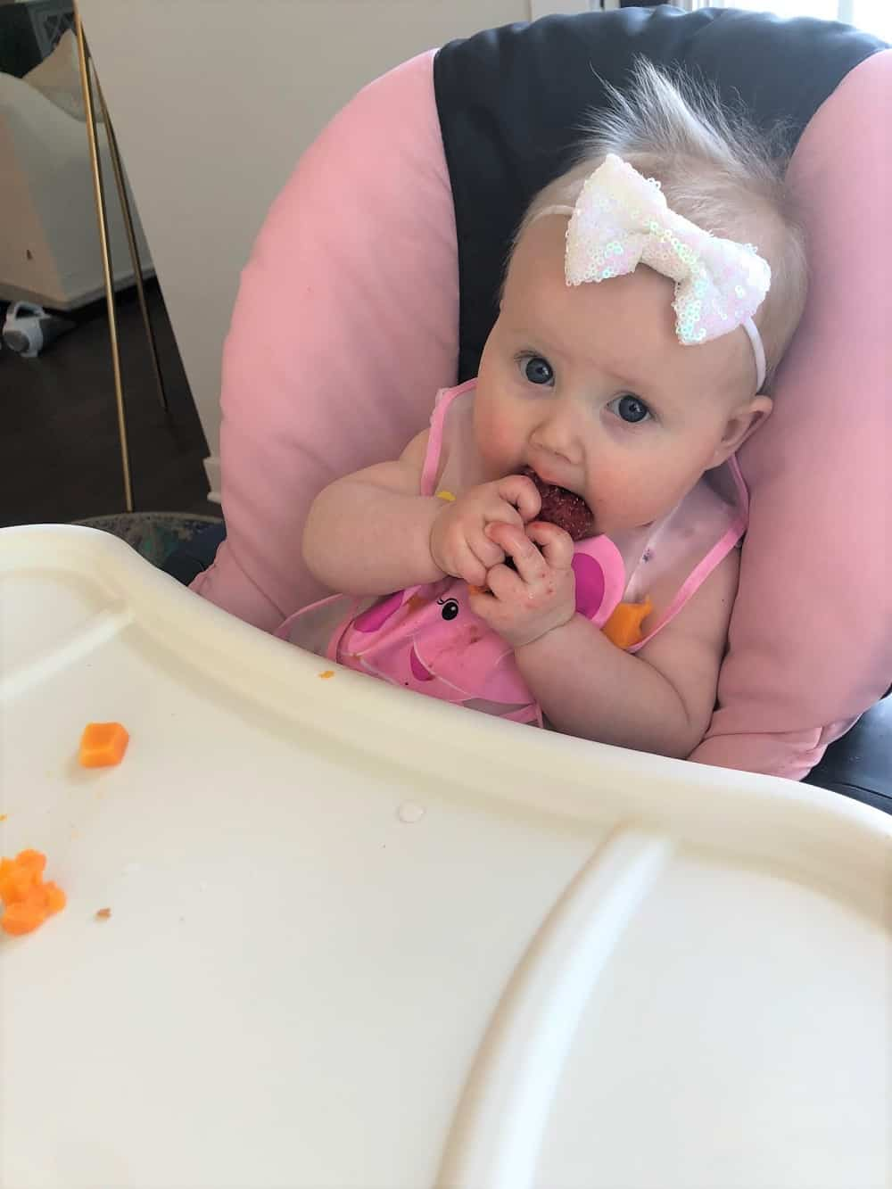 baby eating strawberry in high chair