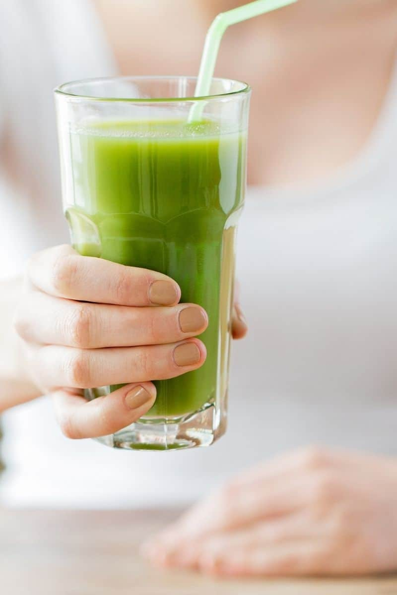 clear glass with green juice and straw
